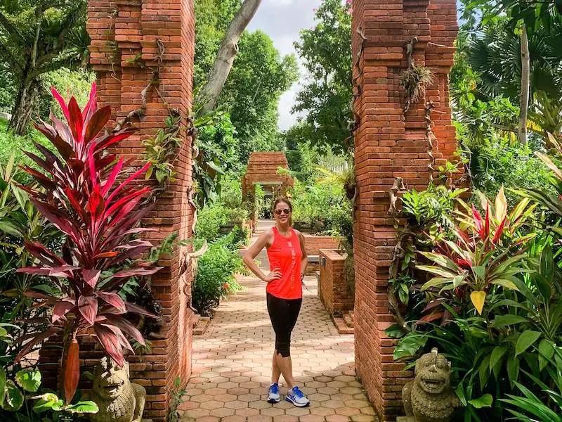 Emma in red top standing in an exotic garden