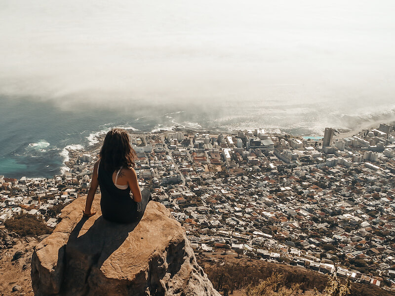 Kathi sitting on top of rock overlooking a city by the ocean
