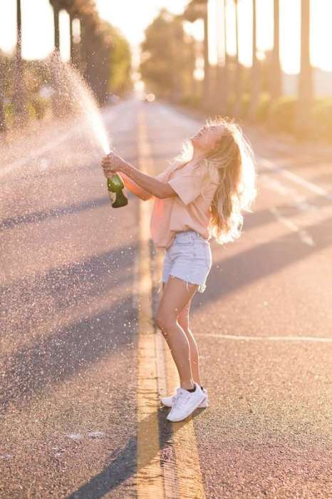 girl popping champagne in street