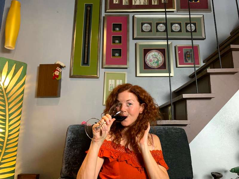 Red head drinking wine with art behind her