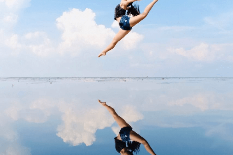 Girl jumping with reflection from Sky Mirror in Malaysia.