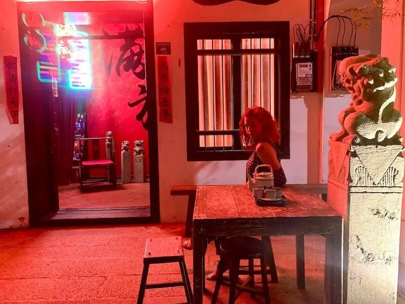 girl sitting outside under red lights