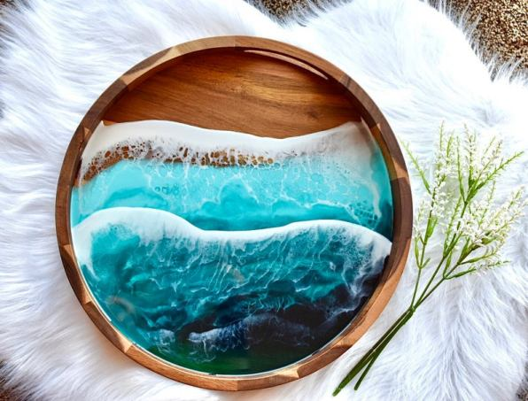 circular wooden tray with blue ocean waves made of epoxy on it. Its a gorgeous gift for beach lovers