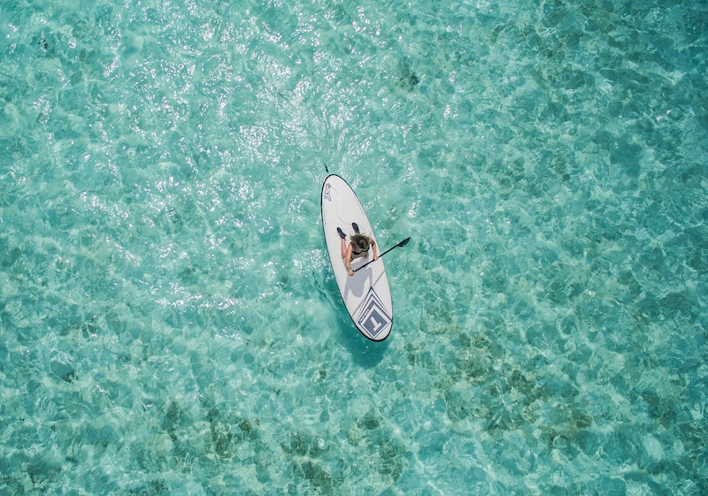 girl paddleboarding over clear blue ocean: living in a foreign country