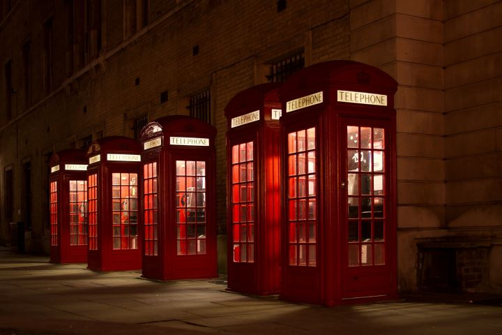 Telephone booths lined up on a city street.