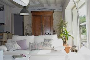 Salon avec canapé moderne qui vient contraster avec l'armoire ancienne. Poutres peintes en gris
