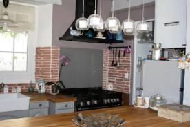 Piano de cuisson noir, pierres de parement, hotte noire, cuisine ancienne.
