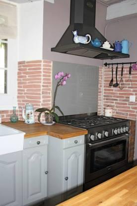 Cuisine: Piano de cuisson noir, pierres de parement, hotte noire, cuisine ancienne.