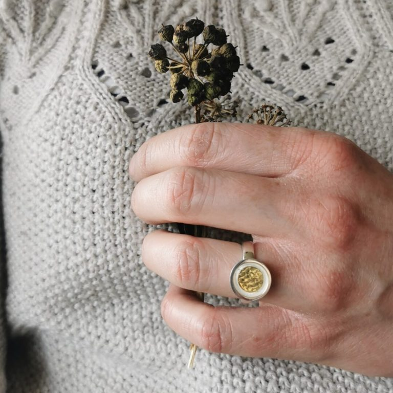 A silver ring with a textured gold centre circle on a hand holding a tried seed pod