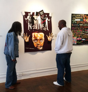 Marion Coleman and Joyce Gordon Gallery curator Eric Murphy in front of Hands Up Don't Shoot by Jackie Houston. To the right can be seen part of Graffiti Art by Frances Porter.