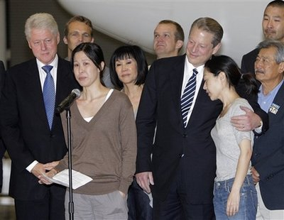 Laura Ling, second left, and Euna Lee, right, two American journalists who were arrested in March after allegedly crossing into North Korea from China, are joined by former President Bill Clinton, and former Vice President Al Gore at Bob Hope Airport in Burbank, Calif., Wednesday, Aug. 5, 2009. Lee and Ling, the two American journalists freed by North Korea, returned home to the United States on Wednesday for a jubilant, emotional reunion with family members and friends they hadn't seen since their arrests nearly five months ago. (AP Photo/Jae C. Hong)