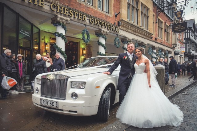 Bride and groom kissing by wedding car outside Chester Grosvenor - professional wedding photography