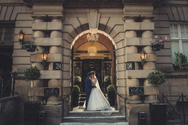Bride and groom kissing in the doorway of the Richmond Hotel in Liverpool