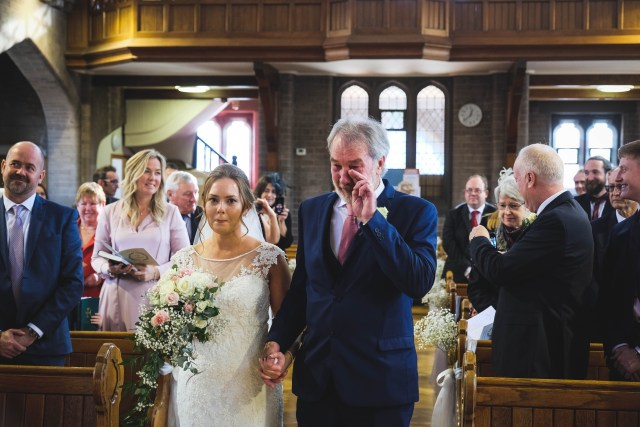 Father of bride crying as he walks bide down the aisle