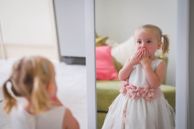 Cute flower-girl looking shocked at her own reflection