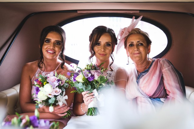 Bride with her mum and bridesmaid in back of wedding car