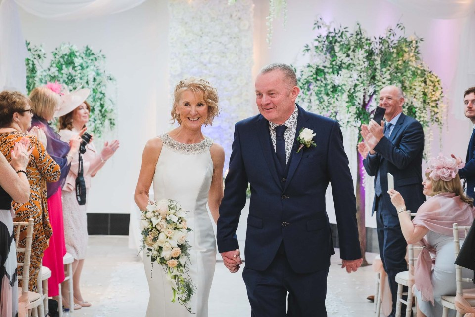 Just married - couple walk down the aisle at Gibbon Bridge Hotel