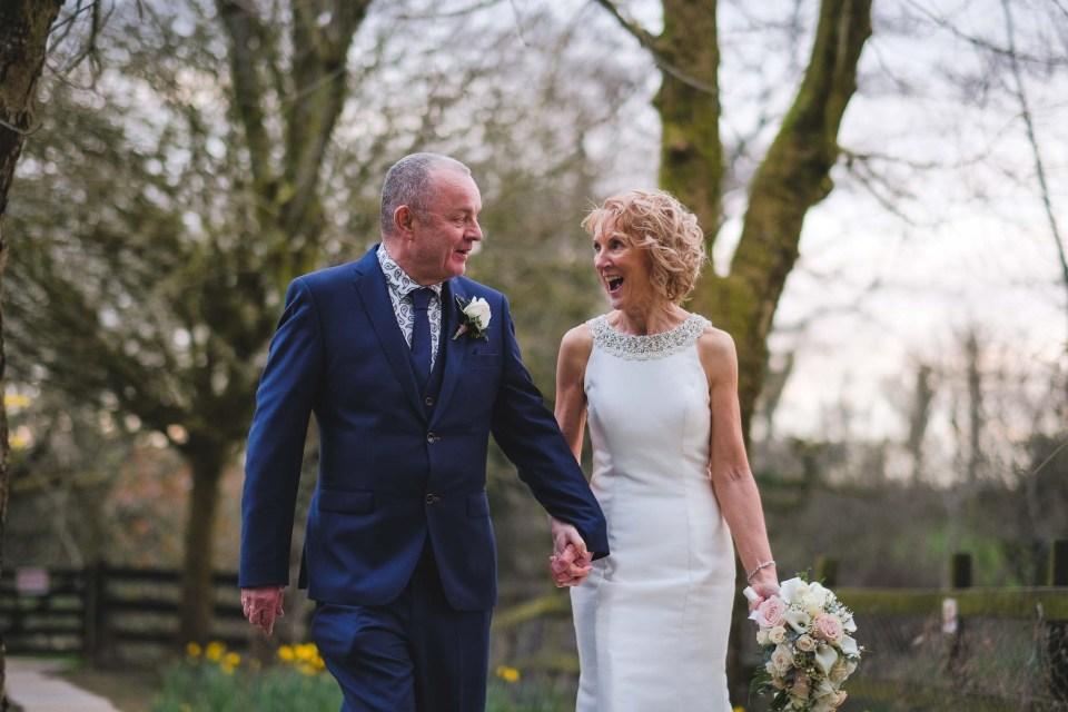 Gibbon Bridge wedding - bride and groom walking through gardens