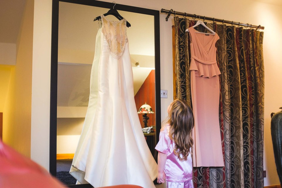 Photograph of flower girl admiring bridal gown