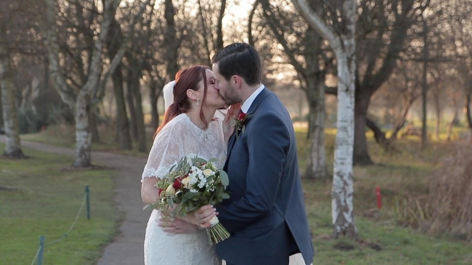 Bride and groom kissing by the golf course at Formby Hall