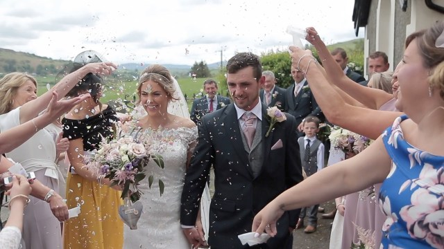 Wedding guests showering confetti over bride and groom in North Wales