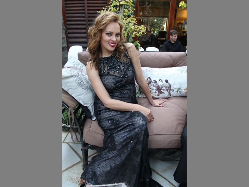 Glitz and glamour... Model Christina Storm is nursing her baby bump with a sit down on the couch.