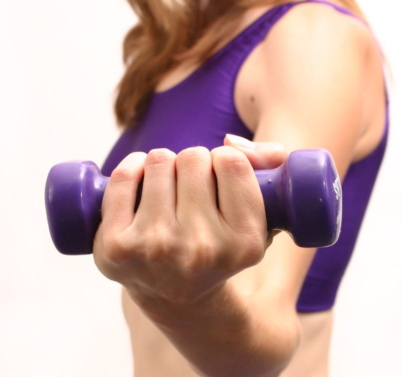 girl lifting a purple hand weight