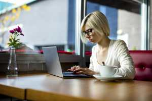 Young focused woman working on laptop with coffee cup on table in cafe, challenges of remote file access