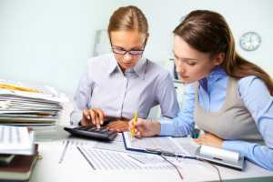 Concentrated business women reviewing accounting report, finding an adhd business coach.