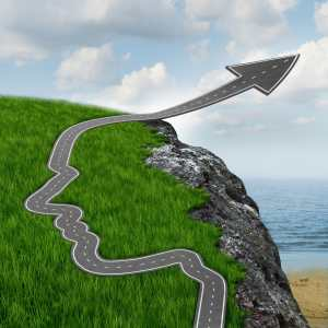 Reduce your business carbon footprint, Success and risk and believing in yourself setting your mind free with a highway in the shape of a human head going up as an arrow over a dangerous rock cliff.