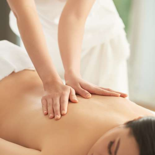 Young Asian woman enjoying back massage in spa salon