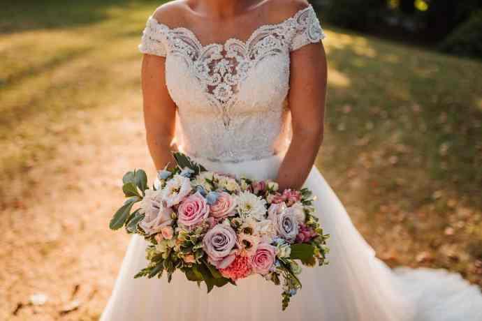Nevesta drži v roki poročni šopek pastelnih barv