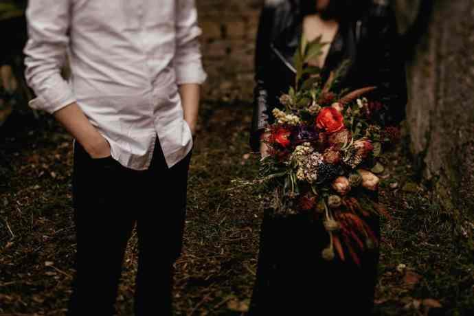 Nevesta in ženin v dark stilu s poročnim šopkom iz ranuncul