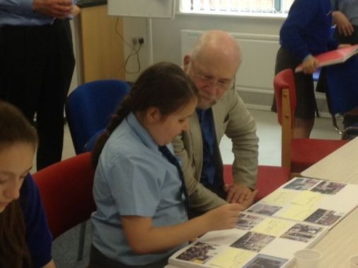 The Rev'd Jim Booth, Chairman of the Liverpool District, talks about the contents of one of the pupil's workbooks.