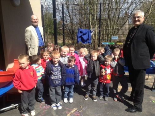 The Rev'ds Dr M Wakelin & Jim Booth visiting Thatto Heath Playdays Nursery children who smile for the camera.