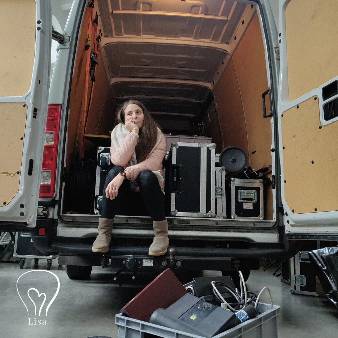 Frau sitzt in Transporter, schaut verzweifelt. Hinter ihr ganz viel Technik Kisten. Vor ihr am Boden eine Kiste mit Mikrofonen.
