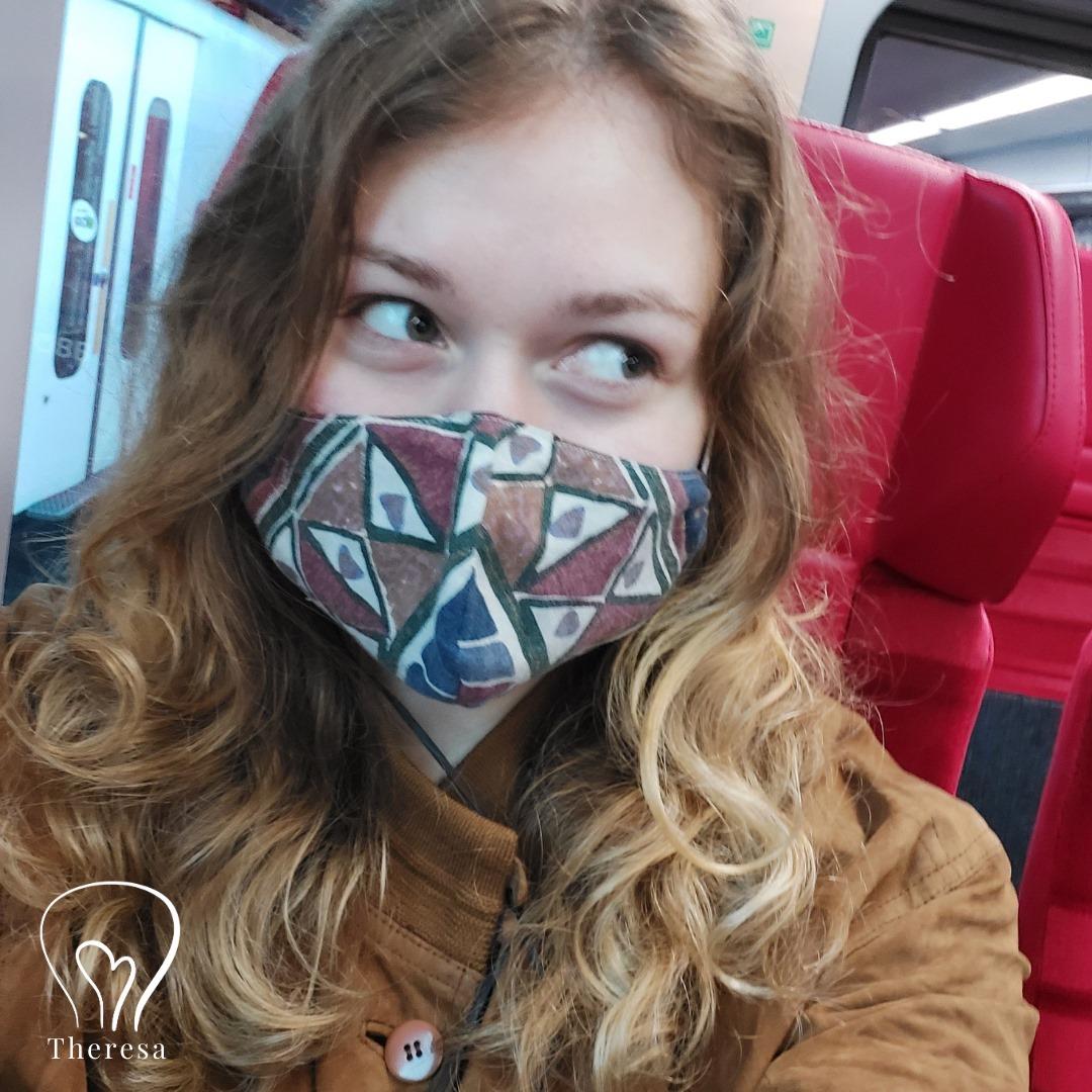 Frau im Zug sitzend. Die Augen schauen genervt und ihre Mimik zeigt lästig an. Sie hat eine Maske auf