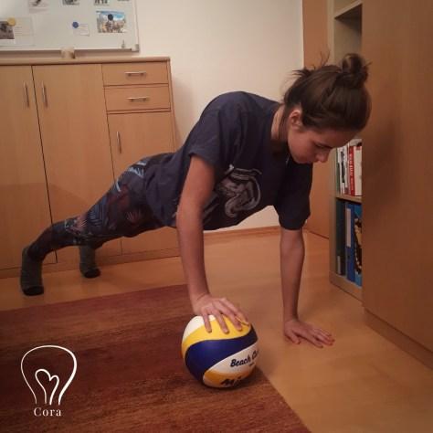 Mädchen in Sportgewand. Gerade macht sie Liegestütz, wobei sie zwischen ihrer rechten Hand und dem Boden einen Volleyball hat.