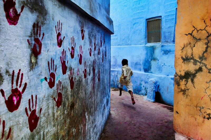 Boy in mid-flight, Jodhpur, India, 2007 At the foot of the vast Mehrangarh Fort, one can find the Blue City, a small tightly knit maze of houses located towards the north of Jodhpur. In one of the narrow alleyways a boy flees McCurry's camera. Balancing three intersecting planes of colour - one of which is covered in stark red handprints - the image pulsates with energy as a young boy dashes through the narrow alleyways. At the foot of the vast Mehrangarh Fort, one can find the Blue City, a small tightly knit maze of houses located towards the north of Jodhpur. Balancing three intersecting planes of colour - one of which is covered in stark red handprints - the image pulsates with energy as a young boy dashes through the narrow alleyways. Phaidon, IP page 6, final print_poster Unguarded Moment_Book Iconic_Book final print_MACRO final print_Genoa final print_Sao Paulo