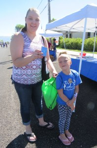 """Jay Lynn Johnson shows """"conversation starter"""" cards, designed to encourage communication between parents and children. Her daughter, Jaide, 7, picked up the cards at the Central Utah Counseling Center booth at the Gunnison Valley Family Health and Safety Fair last Saturday."""