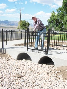 Jay Cluff, a member of the Manti Ad Hoc Committee and primary designer of the Garden of Treasures Under Temple Light, installs railings on the replica two-arch bridge in the garden.