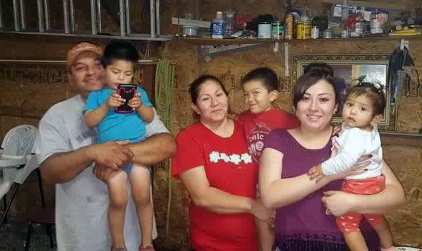 Jose Luis Juarez (left) and his wife Maria Guadalupe's (center, red shirt) and their four children lost all of their possessions in a house fire at an Ephraim mobile home park last Friday.
