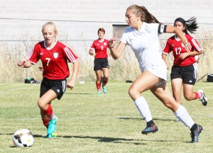 Lady Templar Morganne Stevens (in white) moves the ball downfield in Manti's 7-1 win over Grand.