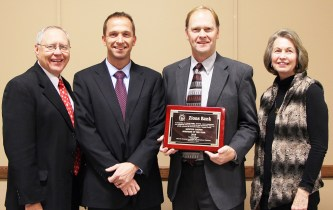 """Sanpete County Commissioner Claudia Jarrett (far right) awards Zions Bank leadership with the """"Business of the Year Award,"""" during the 27th annual Six County Association of Governments recognition banquet. Zions representatives pictured are (L-R) Doug Balch, south central Utah region president; Nate Christensen, Ephraim financial center manager; and David Warren, Manti financial center manager."""