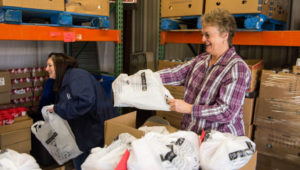 Shannon Cromwell (left) and Susan Brereton (right) are preparing the KidsPacks bags to be taken to local schools to help feed underprivileged children on weekends.