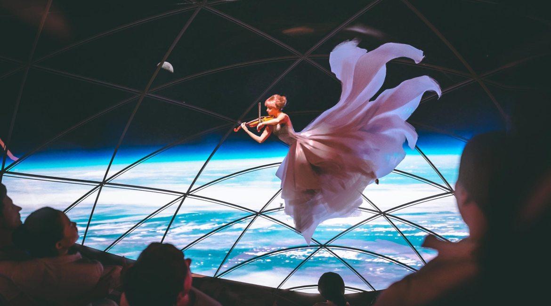 SpaceX BFR, femme jouant de la musique avec un violon dans l'espace au-dessus de la Terre. Découvrez le voyage spatial vers et sur la planète Mars sur Sansible #espace #terre #spacex #bfr #violon #musique #femme #art #sansible