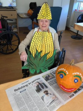 Resident dressed up and painting a Halloween pumpkin