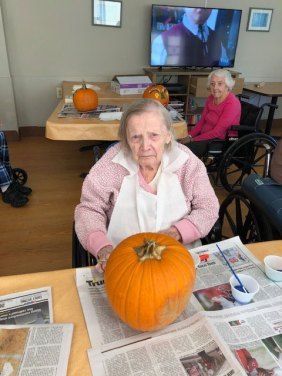 Resident decorating a pumpkin
