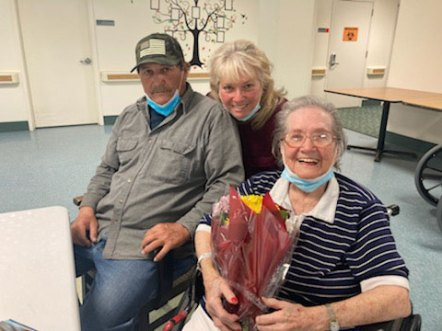 San Simeon female resident holding flowers during Mother's Day visit