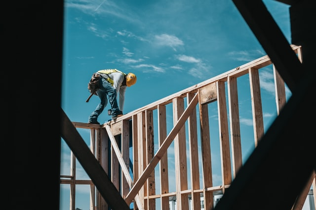 Construction worker builds frame of house